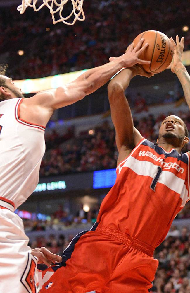Chicago Bulls center Joakim Noah (13) gets a hand on a shot by Washington Wizards forward Trevor Ariza (1) during Game 2 in an opening-round NBA basketball playoff series Tuesday, April 22, 2014, in Chicago. The Wizards won 101-99