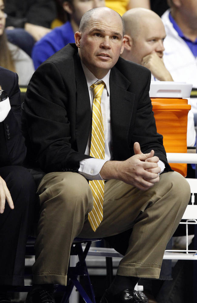 Northern Kentucky head coach Dave Bezold watches his team from the bench during the first half of an NCAA basketball game against Kentucky, Sunday, Nov. 10, 2013, in Lexington, Ky