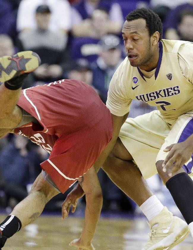 Washington State's DaVonte Lacy, left, tumbles as Washington's Perris Blackwell defends in the second half of an NCAA college basketball game Friday, Feb. 28, 2014, in Seattle. Washington won 72-49