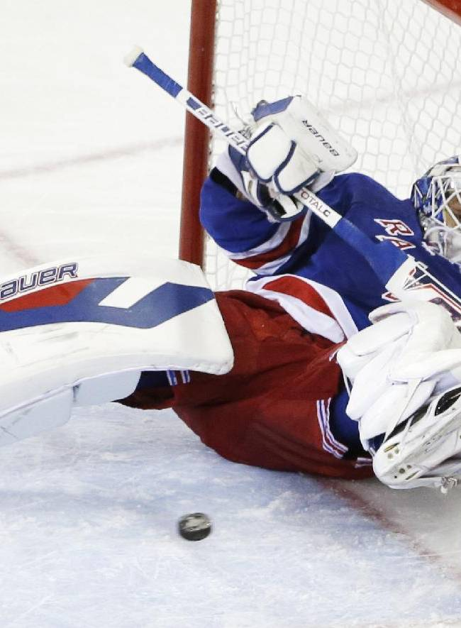 The puck, shot by Los Angeles Kings right wing Dustin Brown, bounces back out of the net after a goal as New York Rangers goalie Henrik Lundqvist (30) falls backward in the second period during Game 4 of the NHL hockey Stanley Cup Final, Wednesday, June 11, 2014, in New York