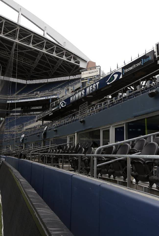 Basilio Valdez, right, cleans off the outdoor seats of field-level suites as he helps prepare CenturyLink Field for the NFL football NFC championship game in Seattle, Tuesday, Jan. 14, 2014. The game will be played between the Seattle Seahawks and the San Francisco 49ers on Sunday