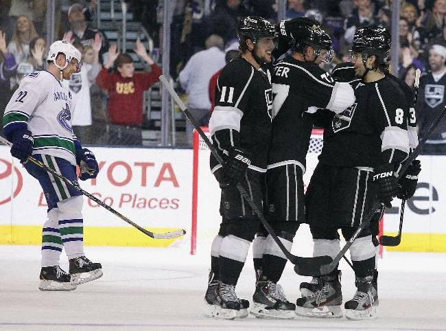 Vancouver Canucks left wing Daniel Sedin (22), of Sweden skates by Los Angeles Kings center Anze Kopitar (11), of Slovenia, celebrating an empty net goal by center Jeff Carter, center, with defenseman Drew Doughty (8) and defenseman Willie Mitchell, far right, during the third period of an NHL hockey game Saturday, Jan. 4, 2014, in Los Angeles. Kings won 3-1