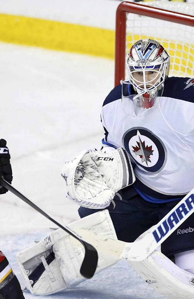 Winnipeg Jets goalie Michael Hutchinson, right, makes a save on a tip by Calgary Flames' Curtis Glencross during the third period of an NHL hockey game in Calgary, Alberta, Friday, April 11, 2014