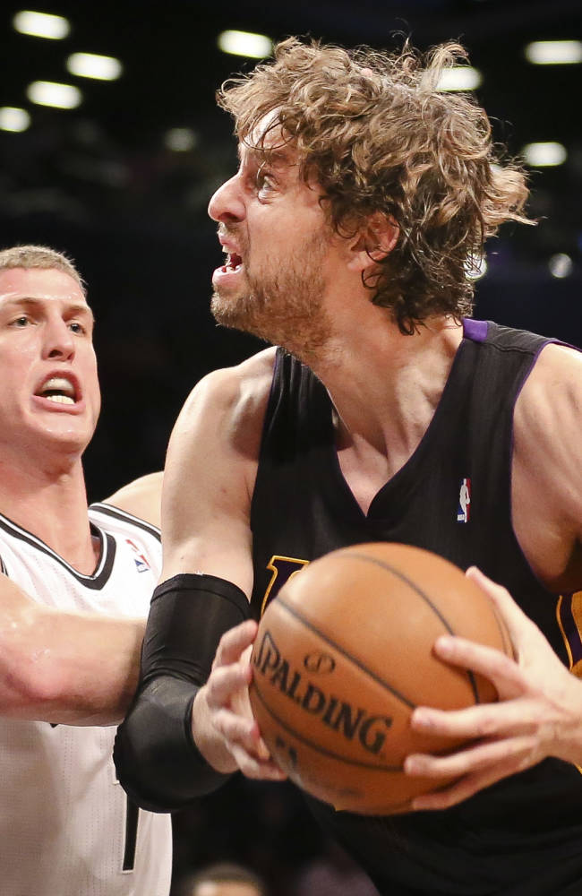 Los Angeles Lakers center Pau Gasol, right, drives to the basket against Brooklyn Nets power forward Mason Plumlee (1) in the fourth quarter of an NBA basketball game at the Barclays Center, Wednesday, Nov. 27, 2013, in New York. The Lakers defeated the Nets 99-94