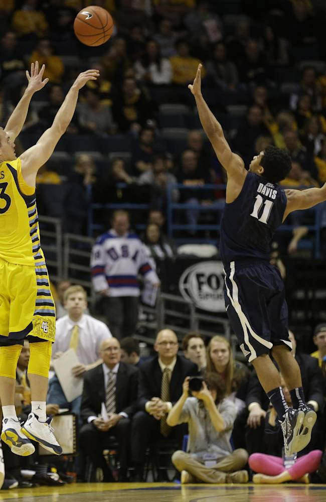CORRECTS MARQUETTE PLAYER TO JAKE THOMAS, INSTEAD OF STEVE TAYLOR JR. - Marquette's Jake Thomas, left, shoots a jumper over Xavier's Dee Davis during the second half of an NCAA college basketball game Saturday, Feb. 15, 2014, in Milwaukee