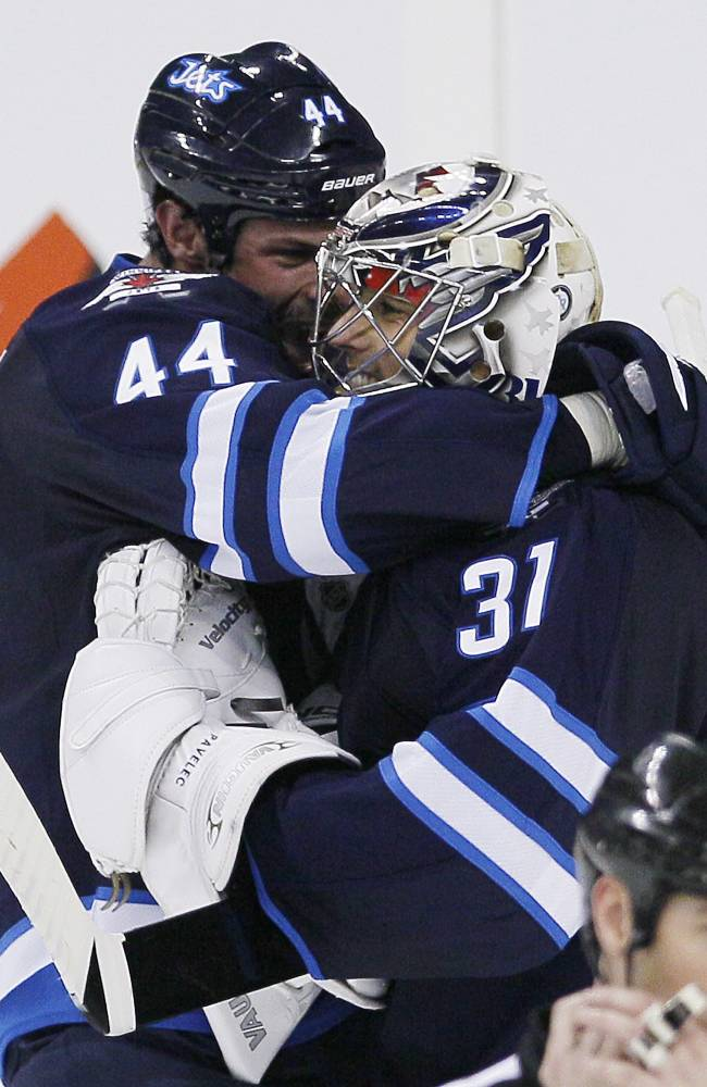 Winnipeg Jets' Zach Bogosian (44) and goaltender Ondrej Pavelec (31) celebrate a win over the St. Louis Blues after a penalty shot shoot-out in an NHL hockey game Friday, Oct. 18, 2013 in Winnipeg, Manitoba