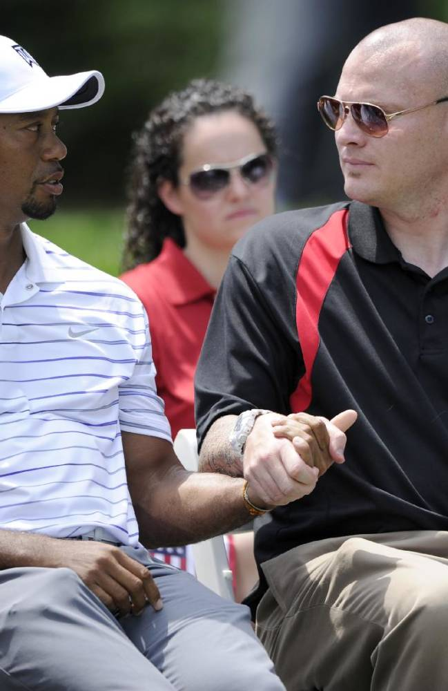 Tiger Woods, left, shakes hands with Marine Capt. Jason Haag, right, during the opening ceremony at the Quicken Loans National golf tournament, Wednesday, June 25, 2014, in Bethesda, Md