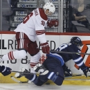 Winnipeg Jets' Tobias Enstrom (39) is dumped into the boards by Phoenix Coyotes' Rob Klinkhammer (36) during first-period NHL hockey game action in Winnipeg, Manitoba, Thursday, Feb. 27, 2014 The Associated Press