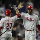 Philadelphia Phillies' Placido Polanco (27) congratulates Phillies' John Mayberry Jr., right, for scoring against the Los Angeles Dodgers during the eighth inning of their baseball game in Los Angeles, Tuesday, July 17, 2012.  (AP Photo/Alex Gallardo)