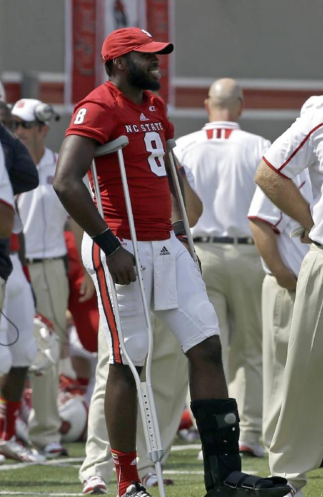 In this Aug. 31, 2013 file photo, North Carolina State quarterback Brandon Mitchell (8) watches from the sidelines during the second half of an NCAA college football game against Louisiana Tech in Raleigh, N.C. Mitchell was injured in the first half. Mitchell said he's pain-free and ready to play against No. 3 Florida State on Saturday, Oct. 26