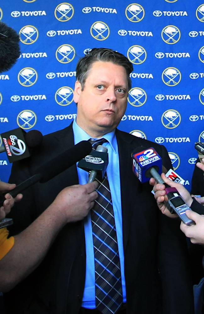 Tim Murray, center, the new Buffalo Sabres hockey team general manager, takes questions from the media at the First Niagara Center in Buffalo, N.Y. , Thursday, Jan. 9, 2014