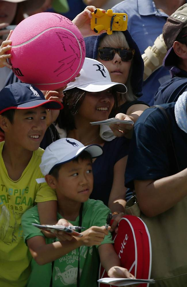 Fans wait for autographs from Kei Nishikori, of Japan, during the first round of the 2014 U.S. Open tennis tournament, Tuesday, Aug. 26, 2014, in New York