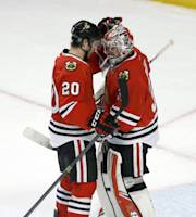 Chicago Blackhawks left wing Brandon Saad (20) and goalie Antti Raanta celebrate the Blackhawks' 1-0 win over the Los Angeles Kings after an NHL hockey game Monday, Dec. 30, 2013, in Chicago. (AP Photo/Charles Rex Arbogast)