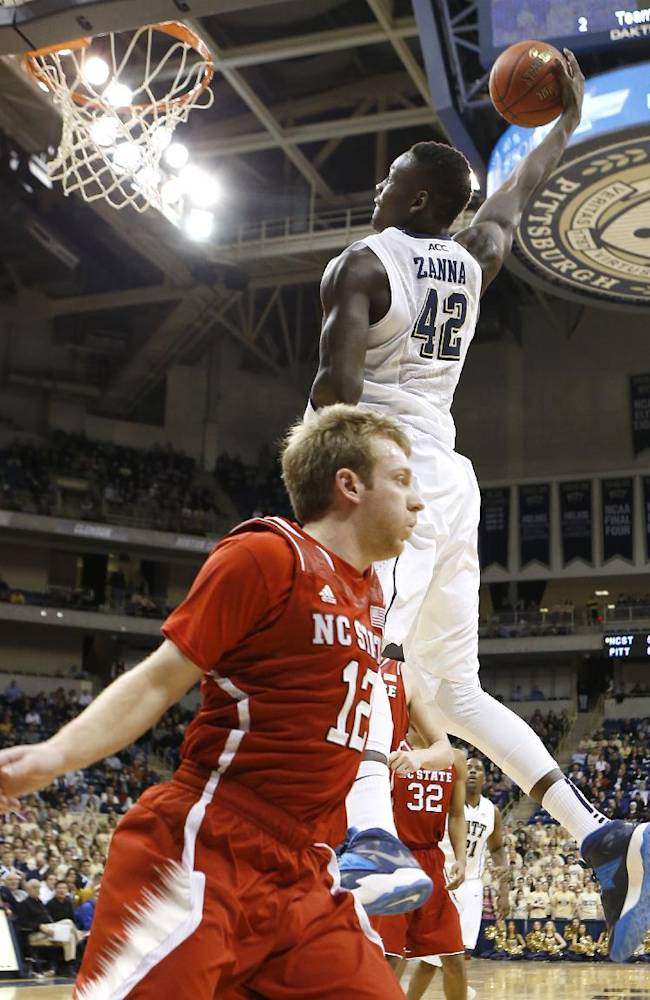 Pittsburgh's Talib Zanna (42) dunks the ball behind North Carolina State's Tyler Lewis (12) during the first half of an NCAA college basketball game on Monday, March 3, 2014, in Pittsburgh