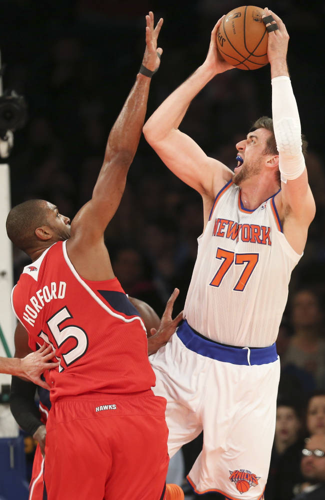 New York Knicks power forward Andrea Bargnani (77) shoots over Atlanta Hawks center Al Horford (15) during the second half of an NBA basketball game Saturday, Dec. 14, 2013, in New York. The Knicks won 111-106