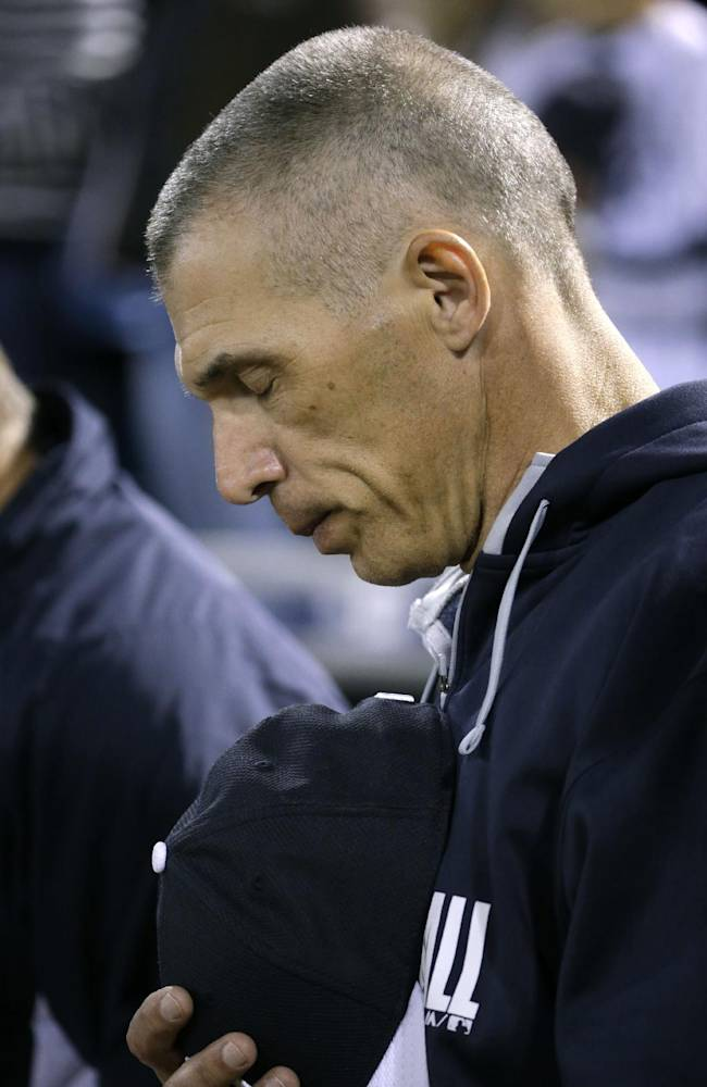New York Yankees manager Joe Girardi observes a moment of silence for Carmen Berra, wife of Yankees Hall of Fame catcher Yogi Berra, who died Thursday before a spring training baseball game against the Detroit Tigers in Tampa, Fla., Friday, March 7, 2014