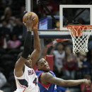 Atlanta Hawks forward Paul Millsap (4) grabs a rebound against Philadelphia 76ers forward Jarvis Varnado (40) in the second half of an NBA basketball game Monday, March 31, 2014, in Atlanta. Atlanta defeated Philadelphia 103-95. Millsap scored 28 points a
