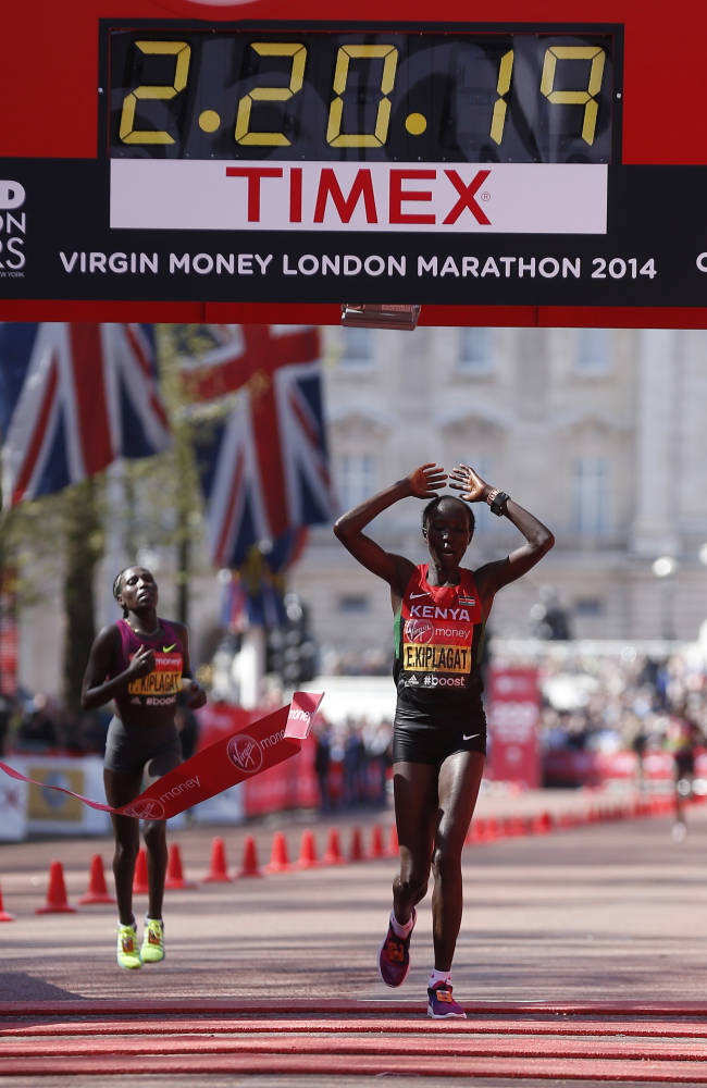 Edna Kiplagat of Kenya, right, celebrates her win in the elite women as she crosses the finish line during the London Marathon in London, Sunday, April 13, 2014. (AP Photo/Sang Tan)
