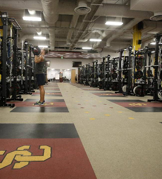 In this Sept. 5, 2013 photo, Jack Wagner, a senior swimmer, lifts weights in the weight room at John McKay Center, an athletic facility on the University of Southern California campus in Los Angeles. With weight rooms as big as football fields, more flat screen TVs than a Best Buy and enough leather furniture to fill Trump Plaza, players have no reason to go back to the dorms