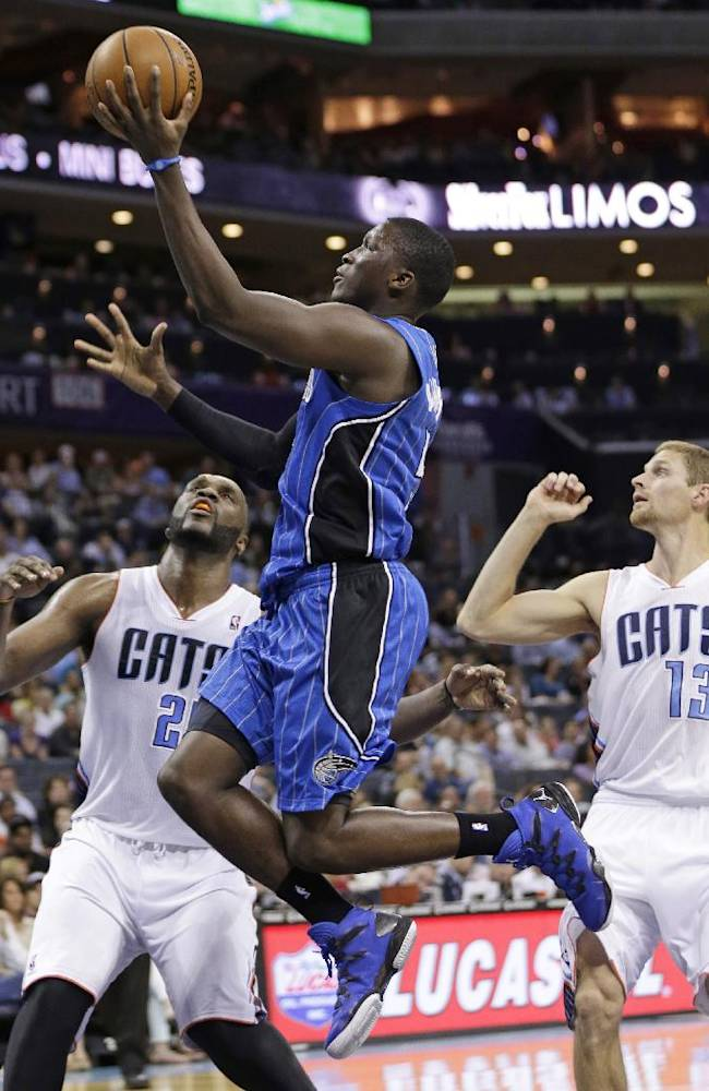 Orlando Magic's Victor Oladipo, center, drives past Charlotte Bobcats' Luke Ridnour, right, and Al Jefferson, left, during the second half of an NBA basketball game in Charlotte, N.C., Friday, April 4, 2014. The Bobcats won 91-80