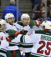 Minnesota Wild's Mikael Granlund (64), Marco Scandella (6), and Jonas Brodin (25) celebrate Dany Heatley's (15) goal against the Colorado Avalanche in the second period during Game 7 of an NHL hockey first-round playoff series on Wednesday, April 30, 2014, in Denver. (AP Photo/Jack Dempsey)