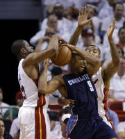 Charlotte Bobcats' Gerald Henderson (9) is defended by Miami Heat's Dwyane Wade, left, and another Heat player during the first half in Game 2 of an opening-round NBA basketball playoff series, Wednesday, April 23, 2014, in Miami. (AP Photo/Lynne Sladky)
