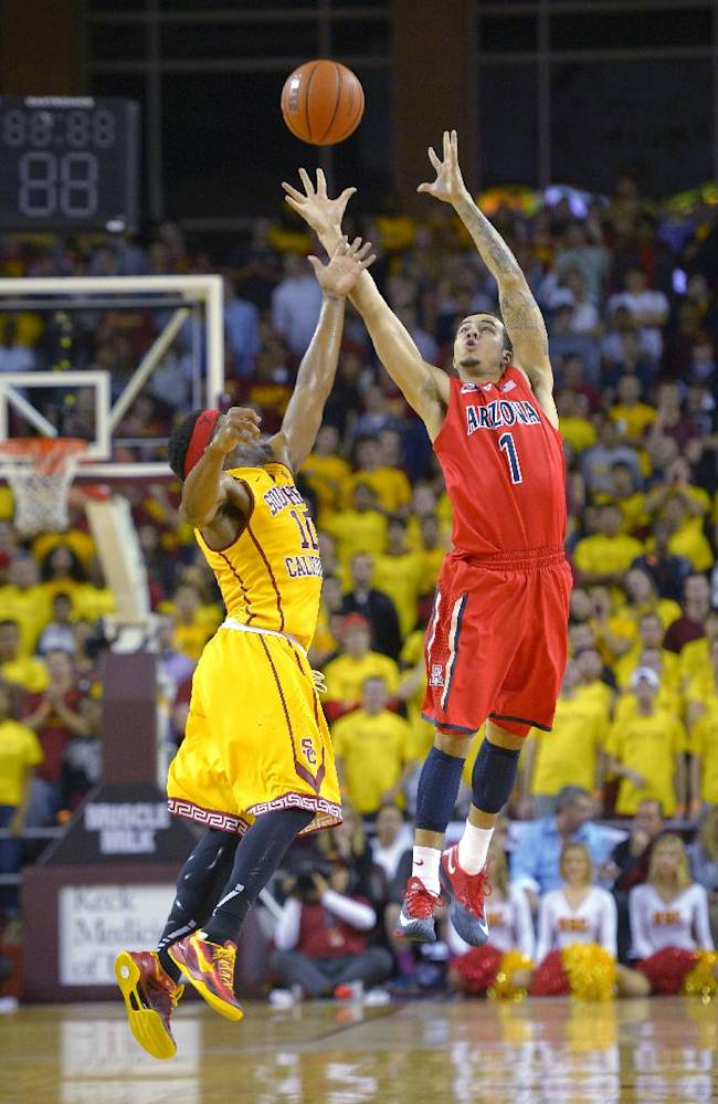 Arizona guard Gabe York, right, catches a pass as Southern California guard Pe'Shon Howard defends during the first half of an NCAA college basketball game, Sunday, Jan. 12, 2014, in Los Angeles