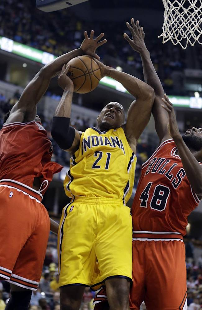 Indiana Pacers forward David West, center, is fouled as he shoots between Chicago Bulls guard Jimmy Butler, left, and center Nazr Mohammed in the second half of an NBA preseason basketball game in Indianapolis, Saturday, Oct. 5, 2013. The Bulls won 82-76