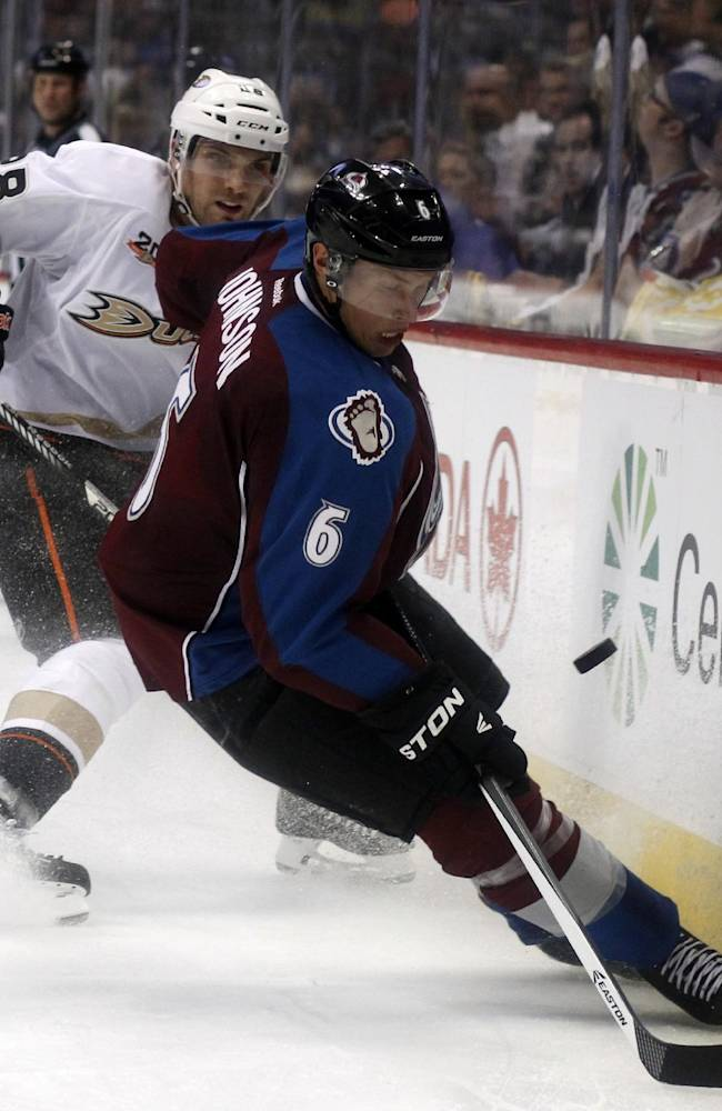 Colorado Avalanche defenseman Erik Johnson, front, takes control of the puck as Anaheim Ducks defenseman Mark Fistric covers in the second period of an NHL hockey game in Denver, Wednesday, Oct. 2, 2013