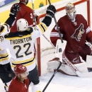 Boston Bruins' Shawn Thornton (22) celebrates his goal against Phoenix Coyotes' Mike Smith, right, with teammate Gregory Campbell, left, while Coyotes' Mike Ribeiro, front, skates past during the third period of an NHL hockey game on Saturday, March 22, 2