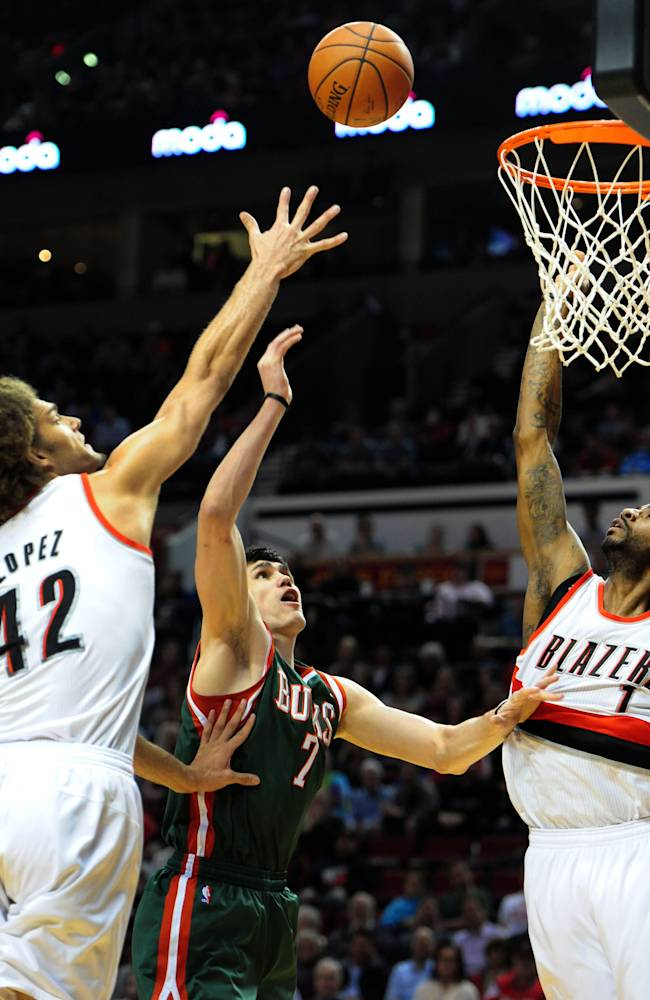 Milwaukee Bucks forward Ersan Ilyasova (7) drives to the basket on Portland Trail Blazers center Robin Lopez (42) and forward Dorell Wright (1) during the first half of an NBA basketball game in Portland, Ore., Tuesday, March 18, 2014