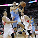 Denver Nuggets' Evan Fournier (94) goes to the basket between Houston Rockets Jeremy Lin, left, and Omri Casspi (18) in the first half of an NBA basketball game Saturday, Nov. 16, 2013, in Houston The Associated Press
