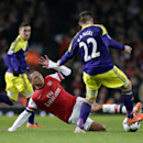 Arsenal's Kieran Gibbs, center, competes for the ball with Swansea City's Angel Rangel during the English Premier League soccer match between Arsenal and Swansea City's at the Emirates Stadium in London, Tuesday, March 25, 2014