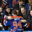 Edmonton Oilers' Ryan Smyth (94) is hugged by teammates after playing his final NHL hockey game, against the Vancouver Canucks in Edmonton, Alberta, Saturday, April 12, 2014. The Oilers won 5-2 The Associated Press