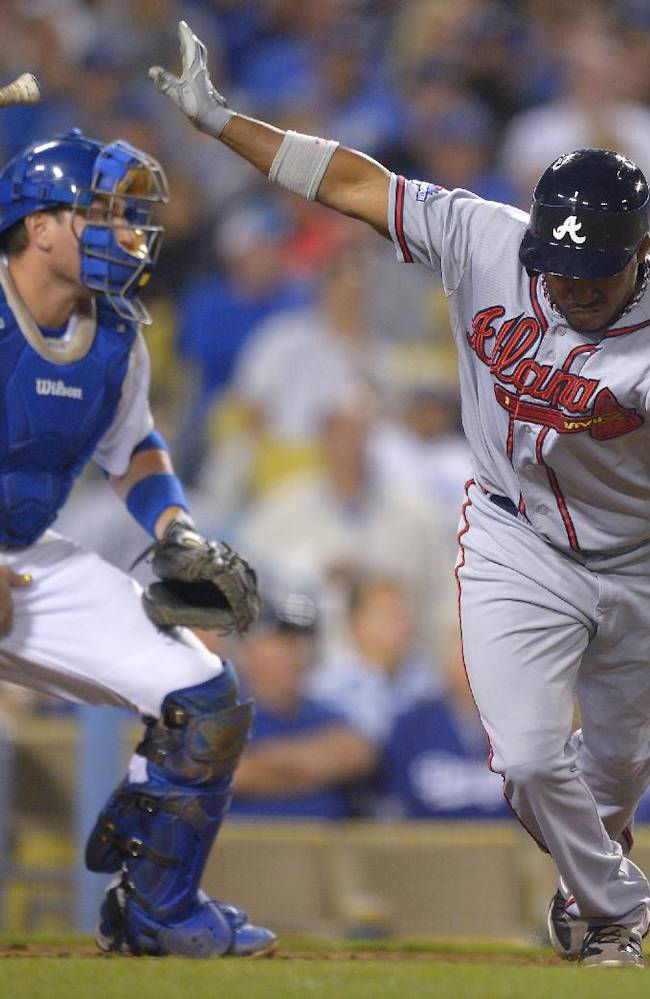 Atlanta Braves' Jose Constanza, right, tosses his bat as Los Angeles Dodgers catcher A.J. Ellis stands up after Constanza hit a single to score Elliot Johnson in the seventh inning of Game 4 in the National League division baseball series, Monday, Oct. 7, 2013, in Los Angeles