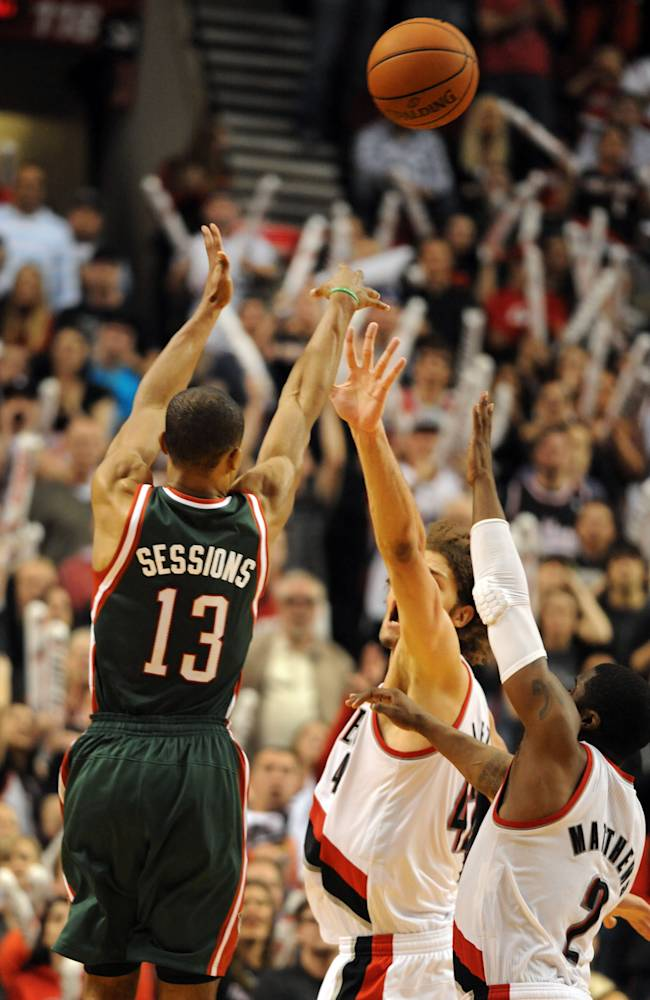 Milwaukee Bucks guard Ramon Sessions (13) hits a three point shot over Portland Trail Blazers center Robin Lopez (42) and guard Wesley Matthews (2) late in the second half of an NBA basketball game in Portland, Ore., Tuesday, March 18, 2014. The Blazers won the game 120-115 in overtime