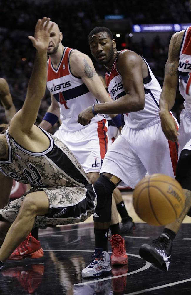 San Antonio Spurs' Tony Parker (9), of France, loses control of the ball as he is pressured by Washington Wizards' Marcin Gortat (4), John Wall, second from right, and Glen Rice (14) during the first half of an NBA basketball game on Wednesday, Nov. 13, 2013, in San Antonio