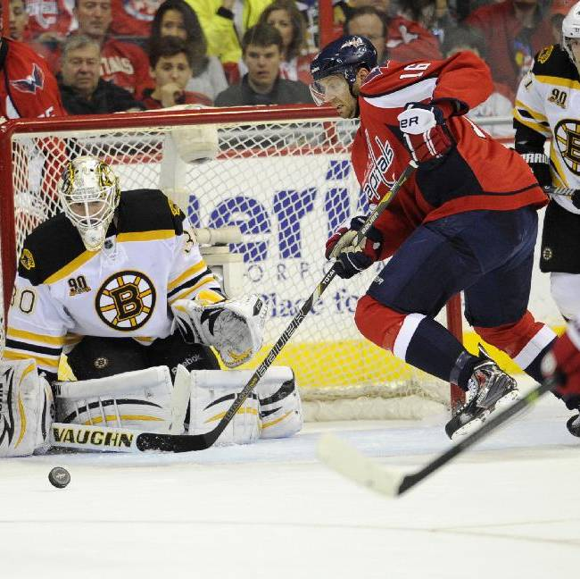 Washington Capitals right wing Eric Fehr (16) chases the puck against Boston Bruins goalie Chad Johnson (30) during the second period of an NHL hockey game, Saturday, March 29, 2014, in Washington. The Bruins won 4-2