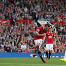 Manchester United's Juan Mata scores against Queens Park Rangers during their English Premier League soccer match at Old Trafford Stadium, Manchester, England, Sunday Sept. 14, 2014