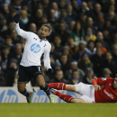 Tottenham Hotspur's Aaron Lennon, left, is tackled by Cardiff City's Declan John during their English Premier League soccer match at White Hart Lane, London, Sunday, March 2, 2014