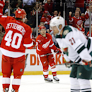 Detroit Red Wings defenseman Xavier Ouellet (61) celebrates his goal with Henrik Zetterberg (40) as Minnesota Wild center Kyle Brodziak (21) looks on in the second period of an NHL hockey game in Detroit Tuesday, Jan. 20, 2015 The Associated Press