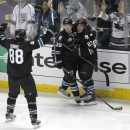 San Jose Sharks center Logan Couture (39) celebrates with Scott Gomez (23) and Brent Burns (88) after Couture scored the winning goal during overtime in Game 3 of their second-round NHL hockey Stanley Cup playoff series, Saturday, May 18, 2013, in San Jose, Calif. San Jose won in overtime 2-1. (AP Photo/Tony Avelar)