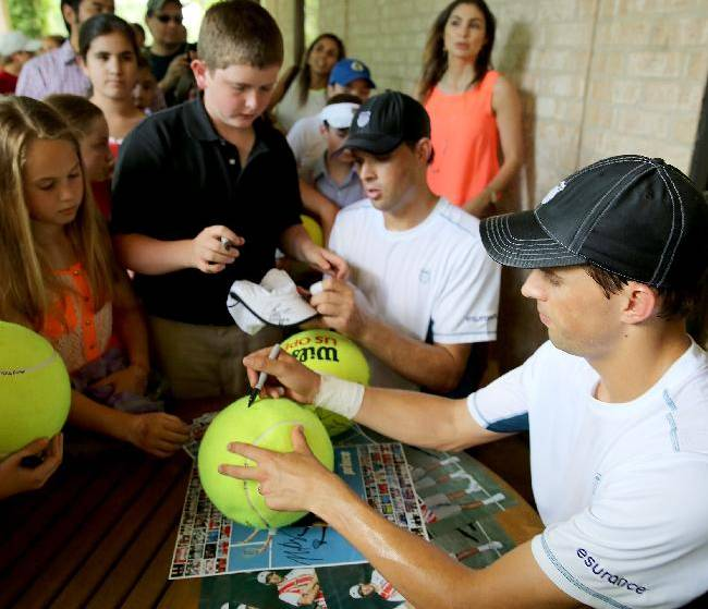 Bob Bryan, left, and Mike Bryan of the U.S. sign autographs after defeating Australians Chris Guccione and Lleyton Hewitt, 7-5, 6-3 on Friday, April 11, 2014 at the U.S. Men's Clay Court Championship at River Oaks in Houston, Texas