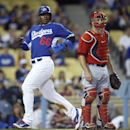 Los Angeles Dodgers' Yasiel Puig, left, scores past Los Angeles Angels catcher Chris Iannetta on a ball hit by Adrian Gonzalez during the second inning of an exhibition baseball game in Los Angeles, Thursday, March 27, 2014 The Associated Press