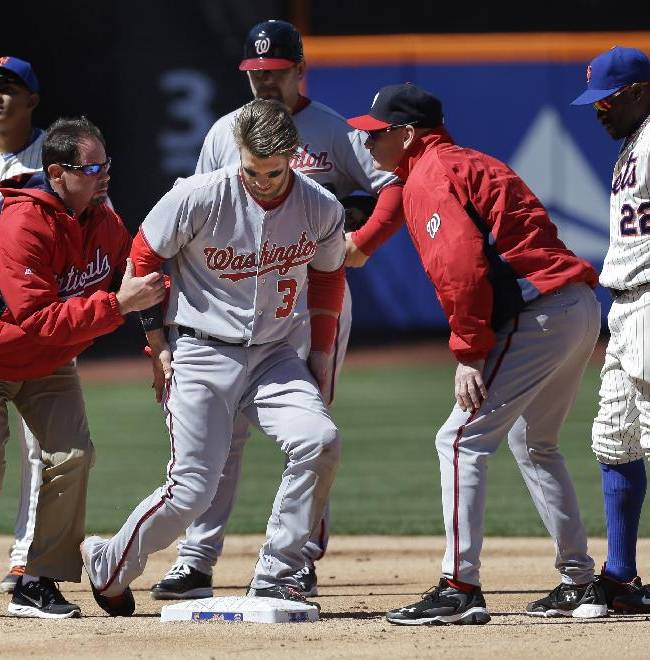 Washington Nationals' Bryce Harper, third from left, is helped off the field after being hit while being tagged out at second base during the second inning of the baseball game against the New York Mets on opening day at Citi Field in New York, Monday, March 31, 2014