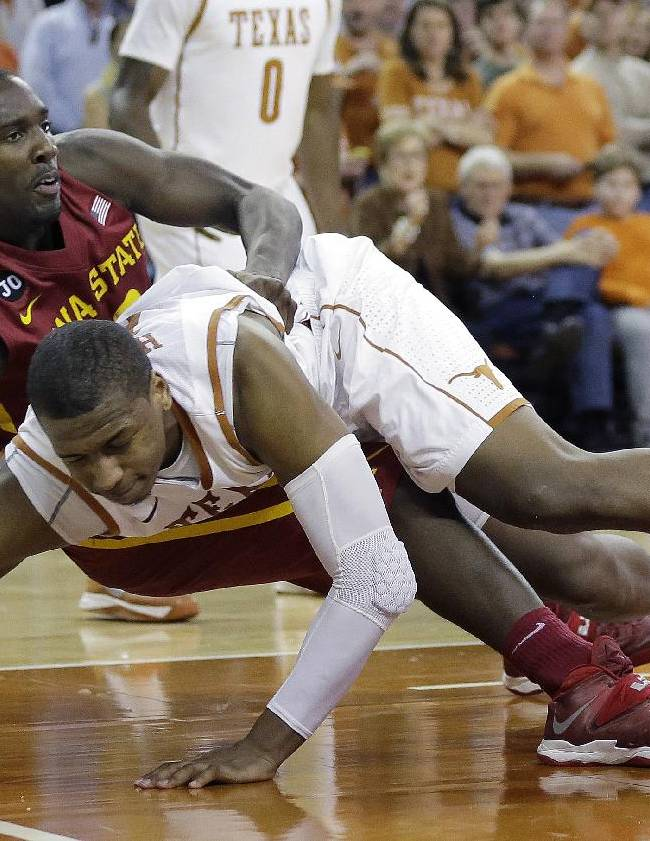 Texas' Jonathan Holmes, front, and Iowa State's Dustin Hogue, fall as they chase a rebound during the second half on an NCAA college basketball game, Saturday,  Jan. 18, 2014, in Austin, Texas. Texas won 86-76