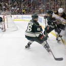Boston Bruins left wing Milan Lucic, right, and Minnesota Wild defensemen Marco Scandella (6) and Jared Spurgeon (46) compete for the puck during the second period of an NHL hockey game in St. Paul, Minn., Wednesday, Dec. 17, 2014. The Bruins won 3-2 in overtime. (AP Photo/Ann Heisenfelt)