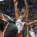 Toronto Raptors' Kyle Lowry, center, is fouled by Milwaukee Bucks' Khris Middleton, left, as Bucks' Giannis Antetokounmpo looks on during first half NBA basketball action in Toronto on Monday, April 14, 2014 The Associated Press