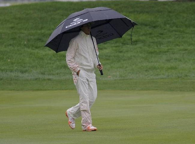 Rickie Fowler walks on the first green under an umbrella as rain falls during the final round of the BMW Championship golf tournament at Conway Farms Golf Club in Lake Forest, Ill., Sunday Sept. 15, 2013