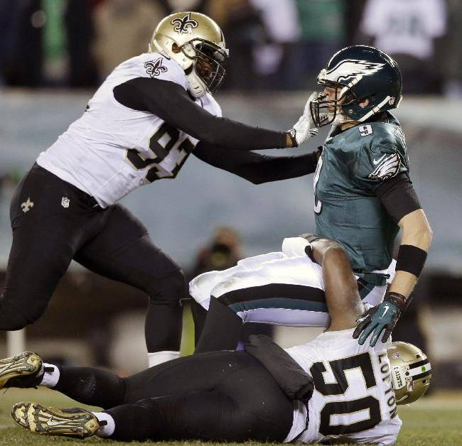 Philadelphia Eagles' Nick Foles, top right, is tackled by New Orleans Saints' Junior Galette, left, and Curtis Lofton during the second half of an NFL wild-card playoff football game, Saturday, Jan. 4, 2014, in Philadelphia